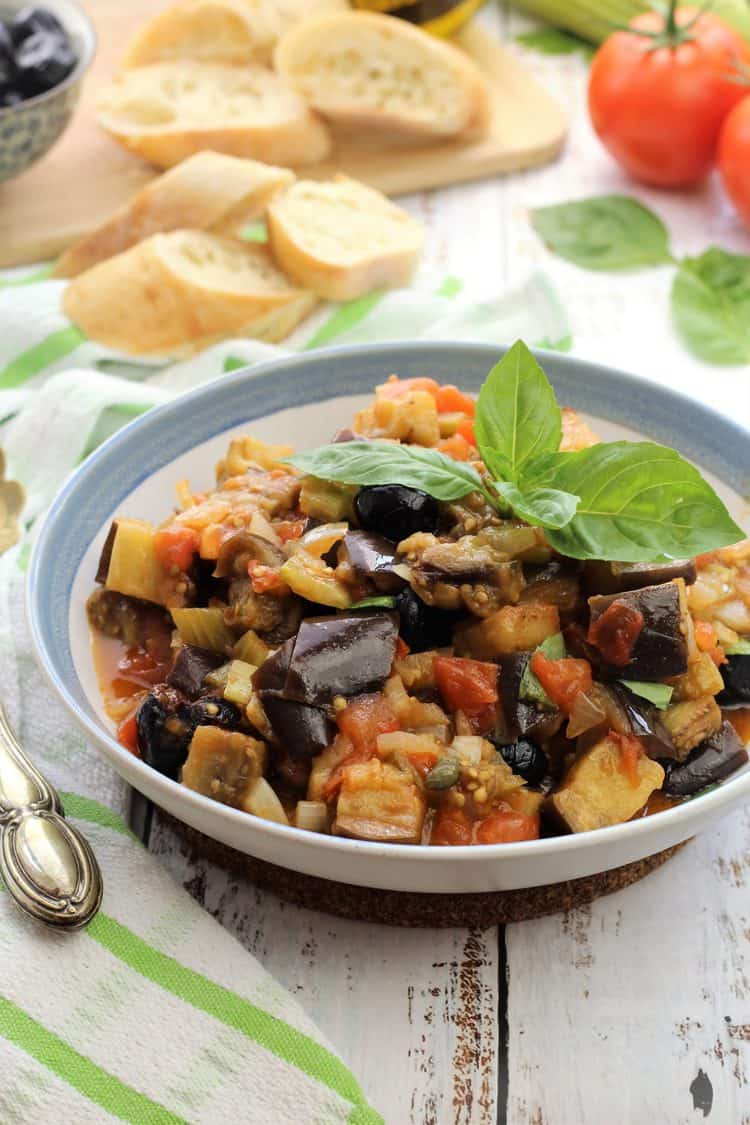 blue rimmed white bowl filled with eggplant caponata topped with basil leaves