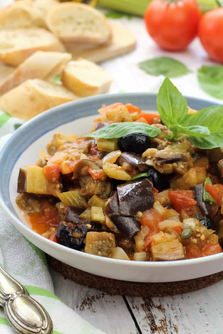 blue rimmed bowl with eggplant, tomato, celery, capers and onions topped with basil