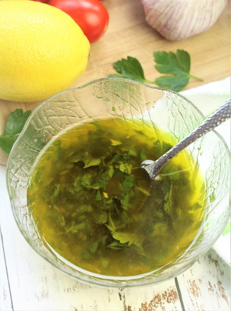 olive oil and parsley dressing in bowl with spoon in it