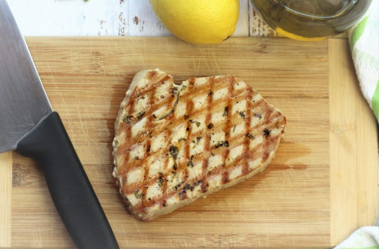 grilled tuna steak on wood board with knife on side