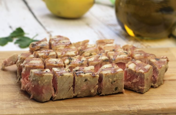 grilled tuna steak on wood board cut into cubes