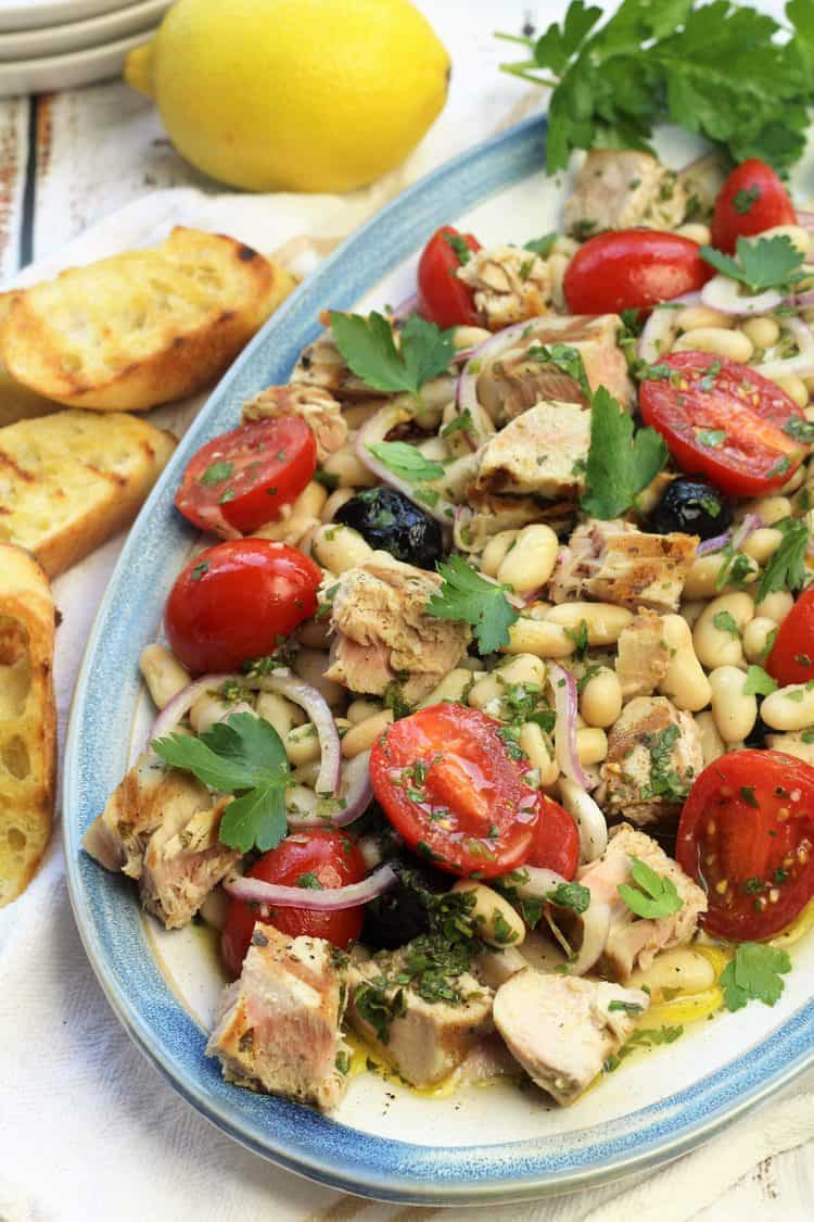 oval platter with grilled tuna and white bean salad surrounded by crusty bread and lemon