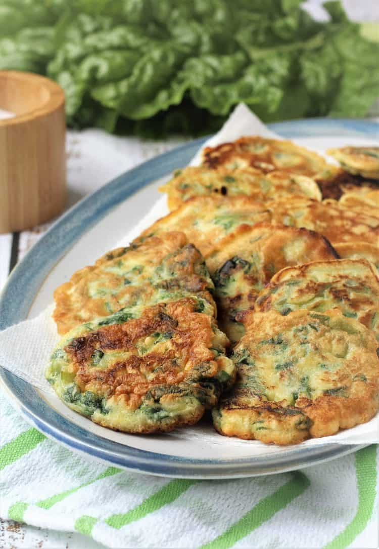 swiss chard fritters layered in blue rimmed platter