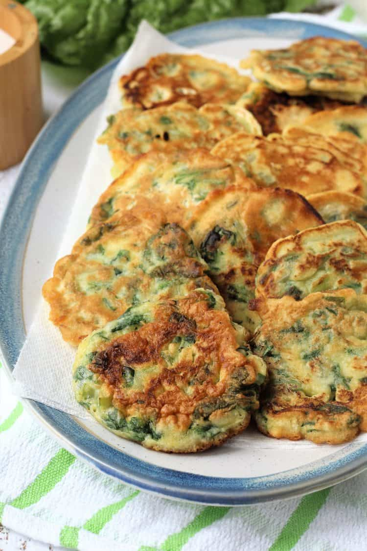 swiss chard frittelle layered in blue rimmed oval plate