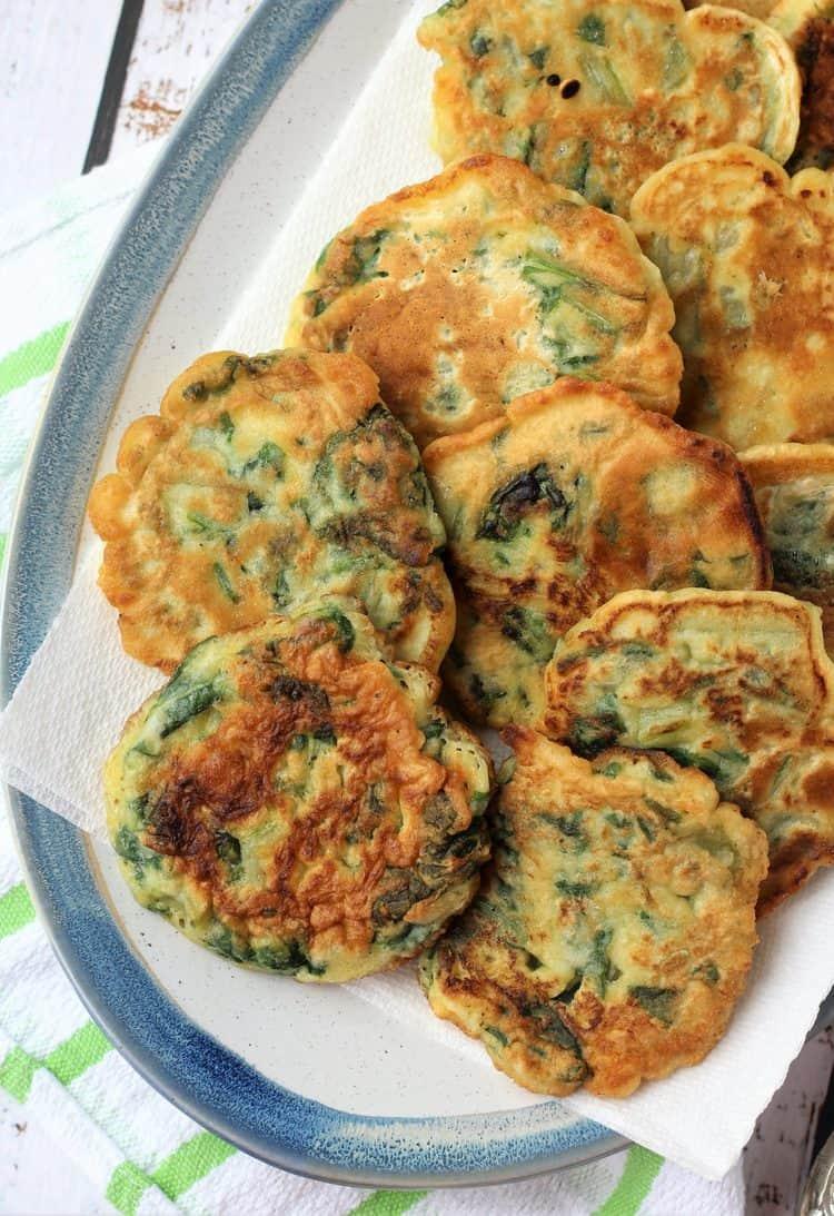 swiss chard crispeddi layered in blue rimmed oval dish
