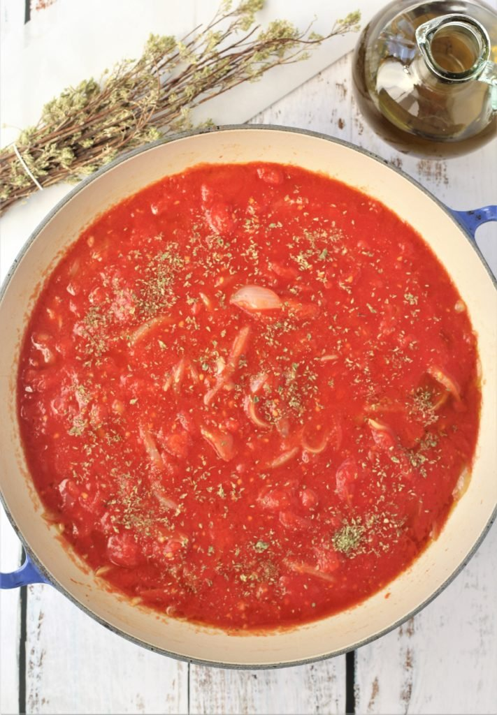 large skillet filled with simmering tomato sauce with oregano branches and olive oil bottle on side