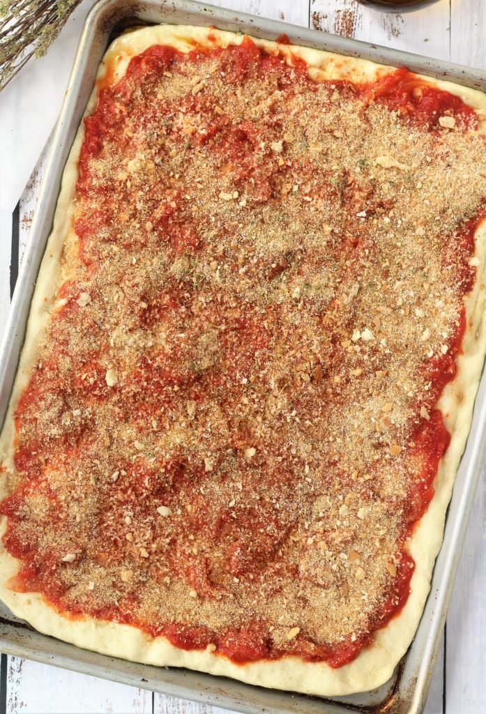 rectangular pizza dough topped with tomato sauce and breadcrumbs