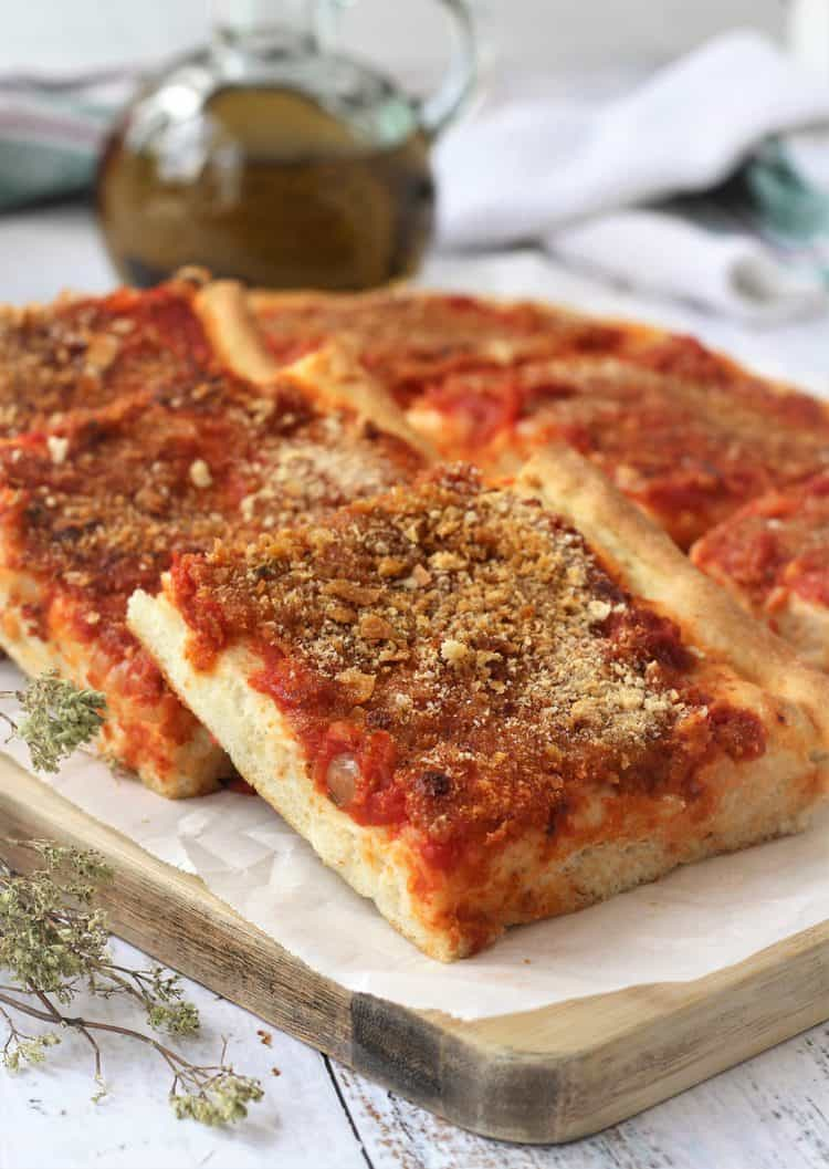tomato and breadcrumb topped pizza squares overlapped on wood board with oregano branches on side