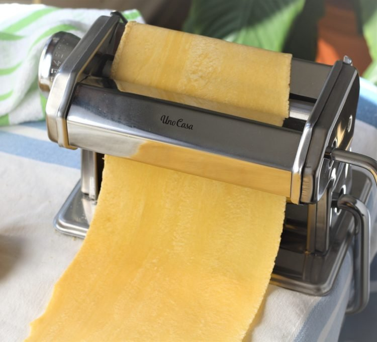 pasta maker with sheet of pasta dough through the rollers