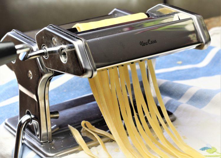 cutting pasta dough into tagliatelle with pasta maker