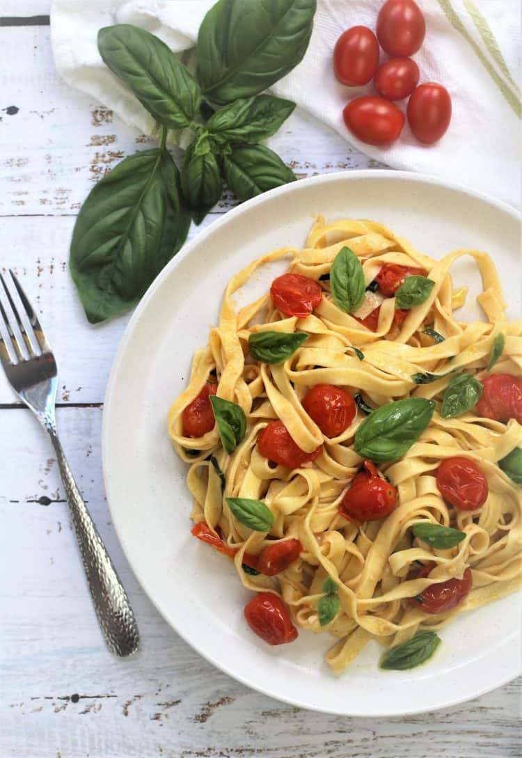 white plate filled with Homemade Tagliatelle with Cherry Tomatoes, Garlic and Basil with fork on side and basil leaves and cherry tomatoes behind it