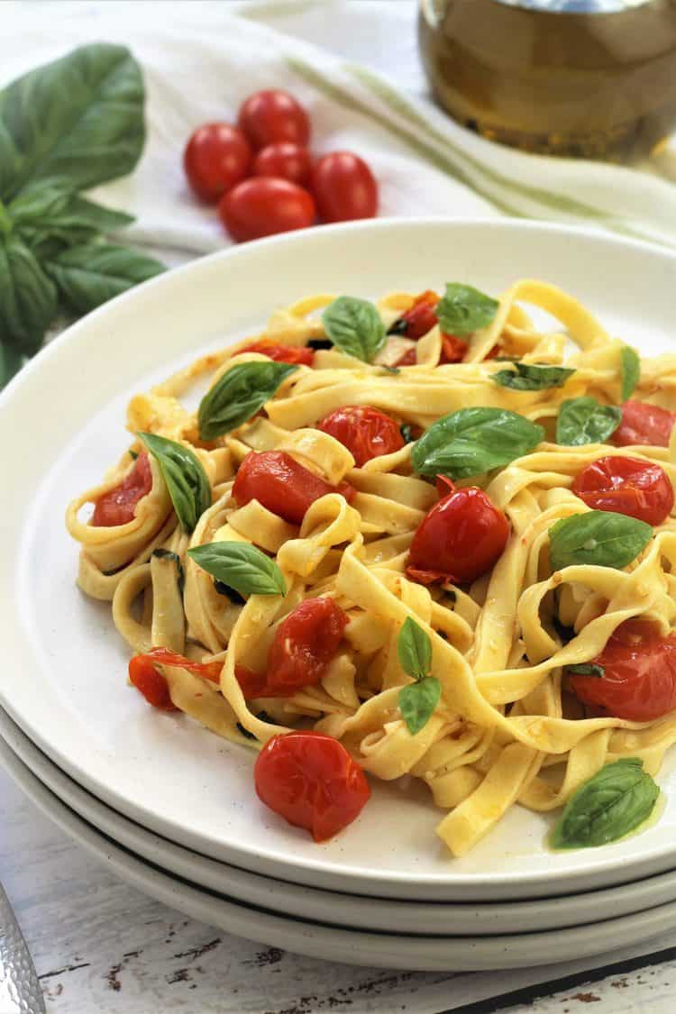 white plate filled with tagliatelle pasta with cherry tomatoes and basil leaves