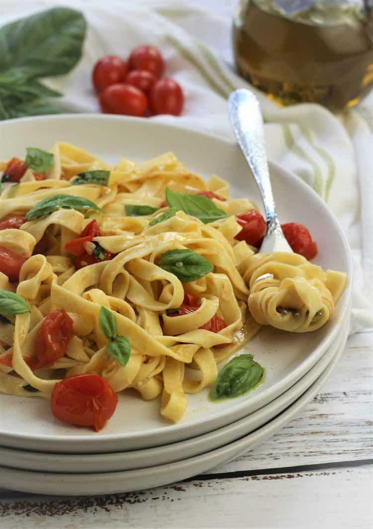 fork twirled with tagliatelle pasta on plate with tagliatelle, cherry tomatoes and basil leaves