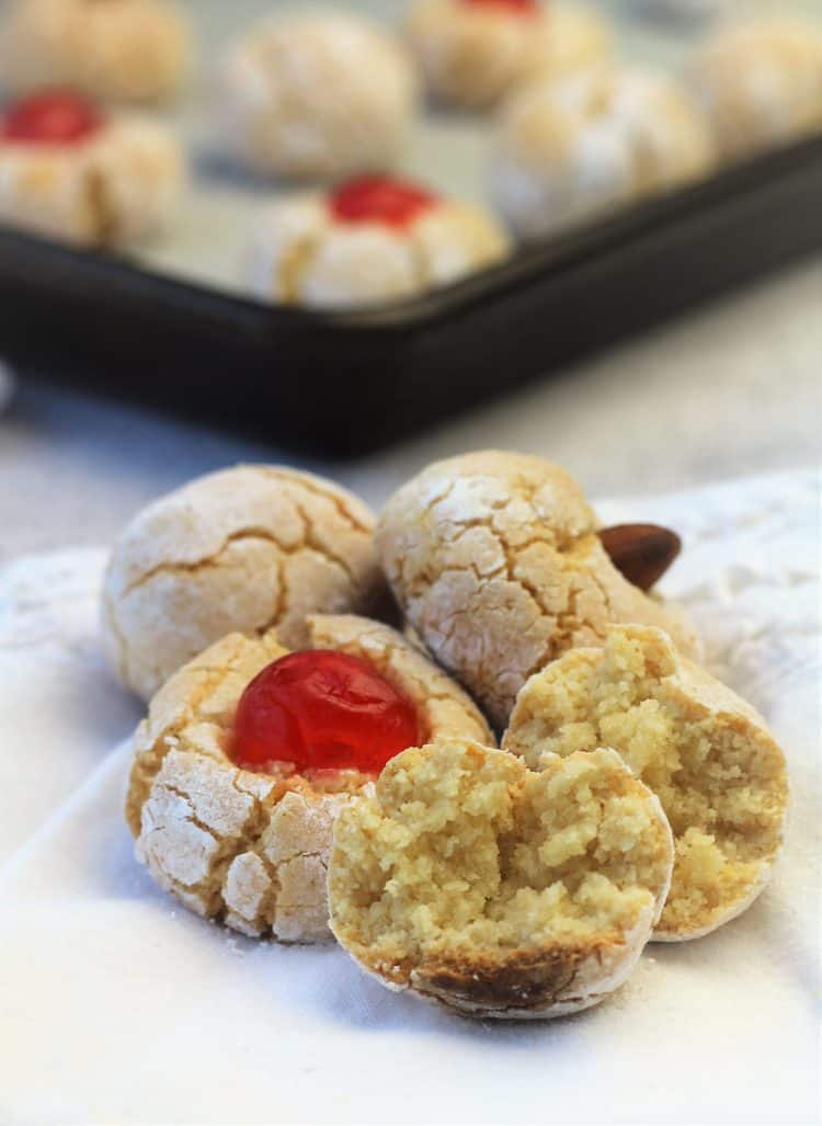 amaretti cookies with one cut in half piled on napkin