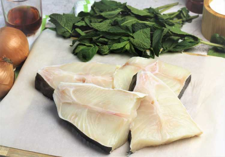 fresh halibut steaks on parchment paper surrounded by mint leaves, onions and glass with vinegar