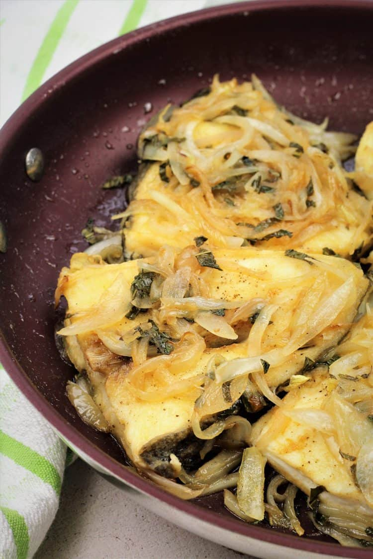 skillet with halibut steaks covered in sliced onions and mint