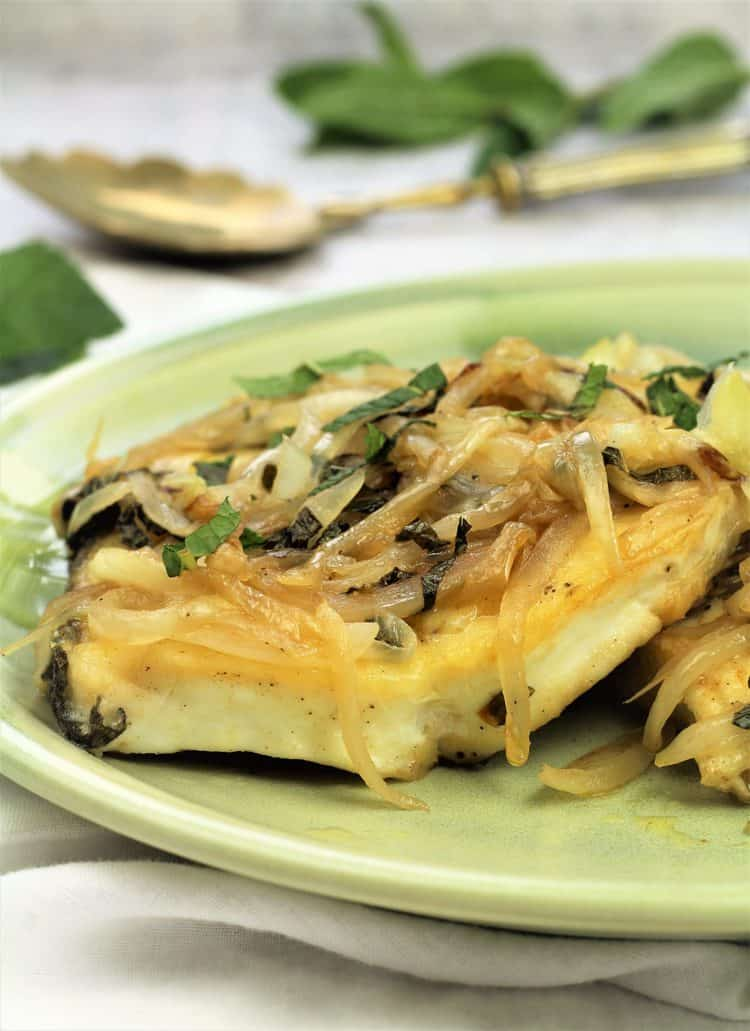 halibut steak topped with onions and mint on green plate