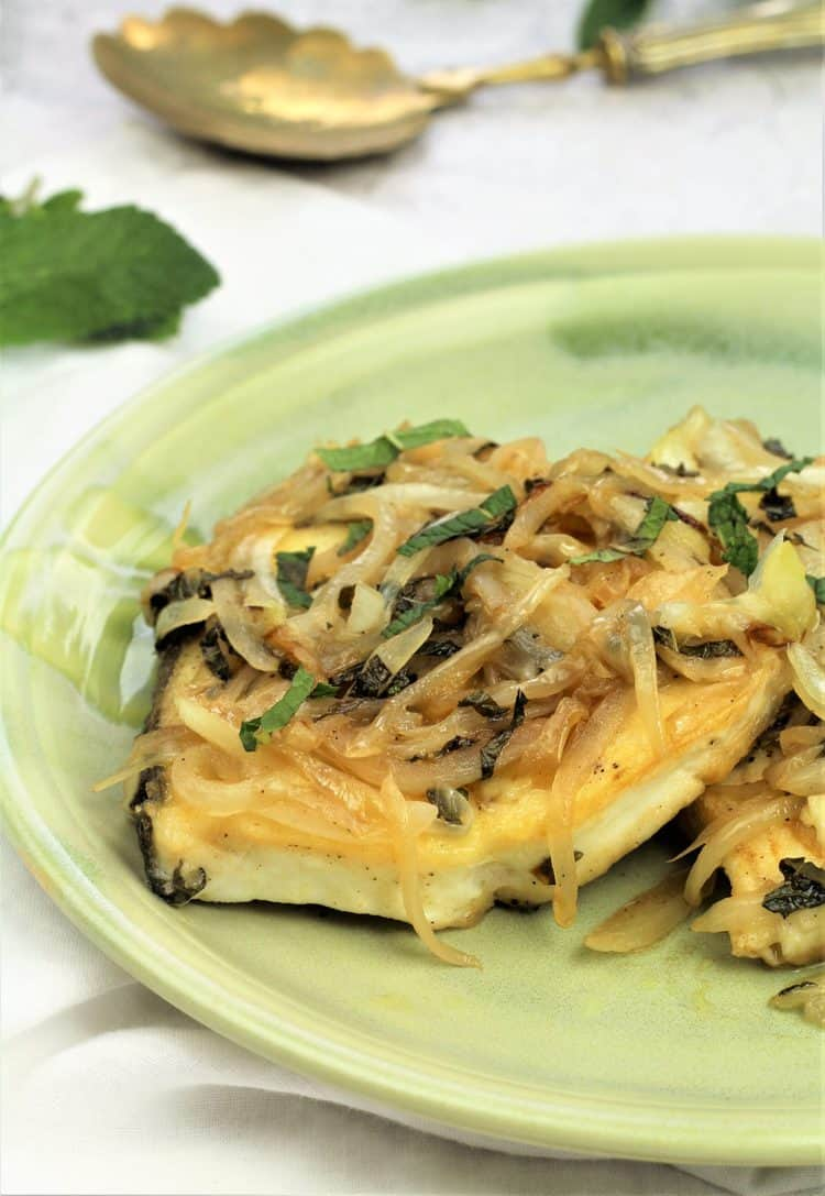 Sicilian fish topped with onions, mint and vinegar on green plate