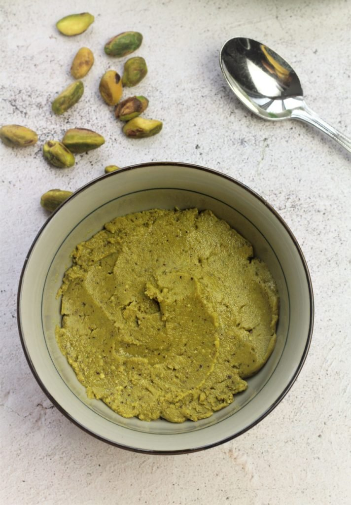 bowl filled with pistachio paste surrounded by shelled pistachios and spoon