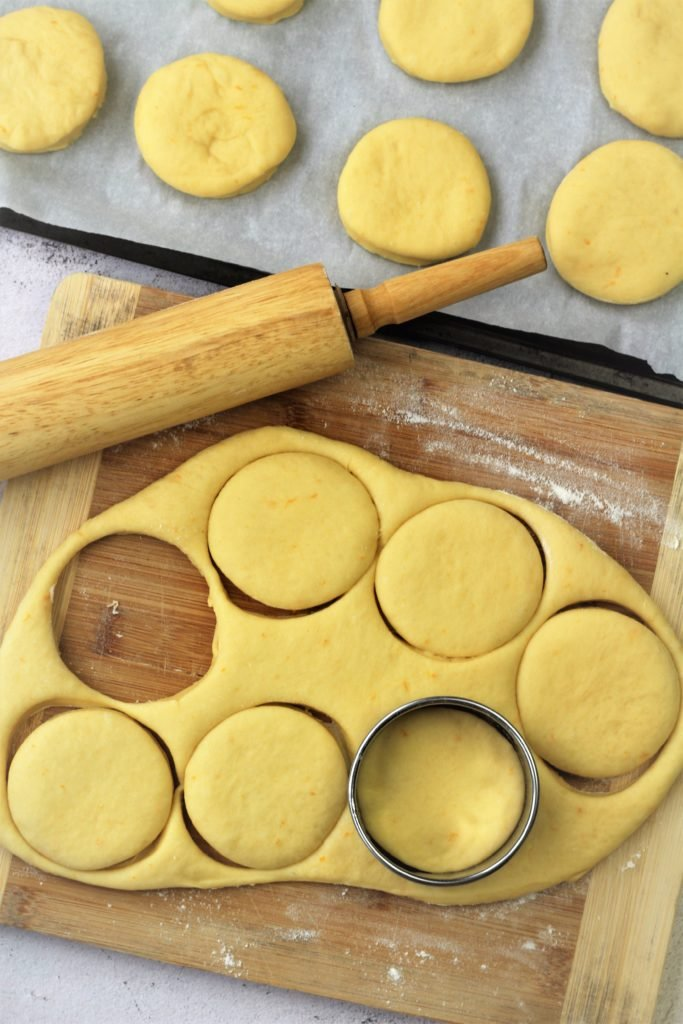 cutting doughnuts with cookie cutter on wood board with rolling pin on side