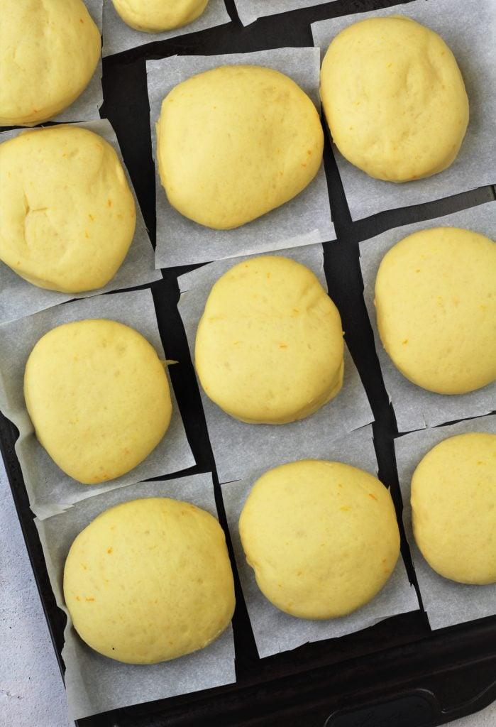 proofed bomboloni doughnuts on parchment paper squares