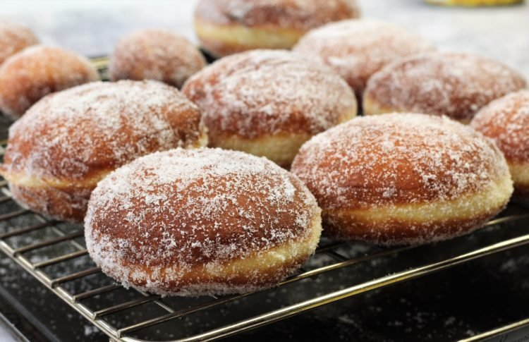 bomboloni doughnuts covered in sugar on wire rack