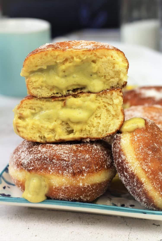 pistachio custard filled bomboloni cut open piled on doughnuts