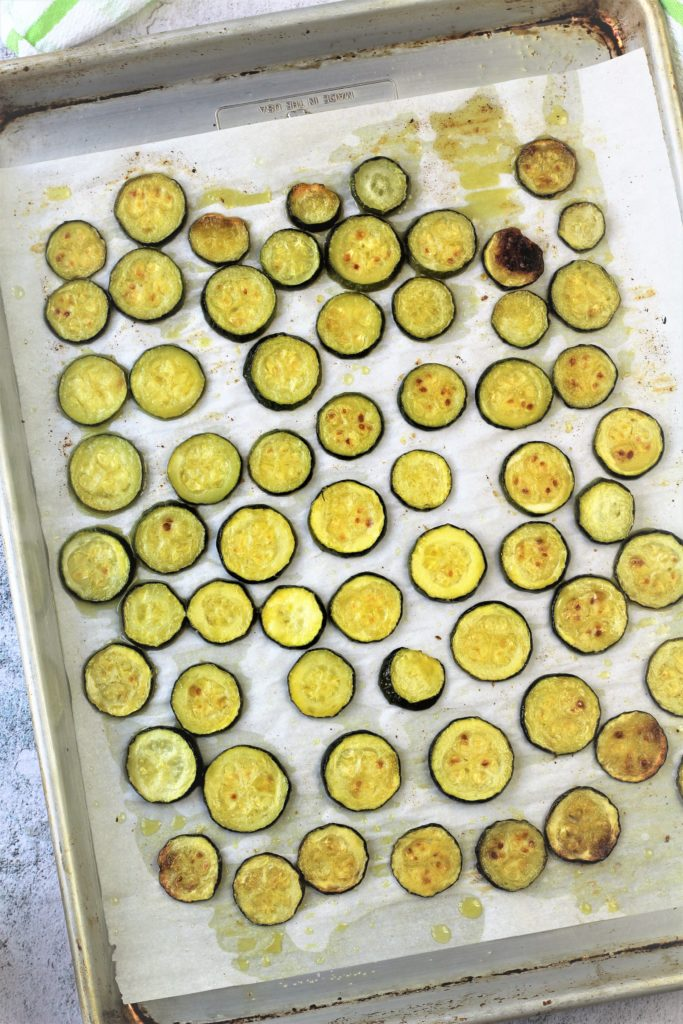 roasted zucchini rounds on parchment paper covered baking sheet