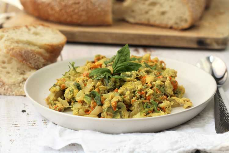 zucchini blossom and egg scramble topped with basil leaves in white plate with bread slices