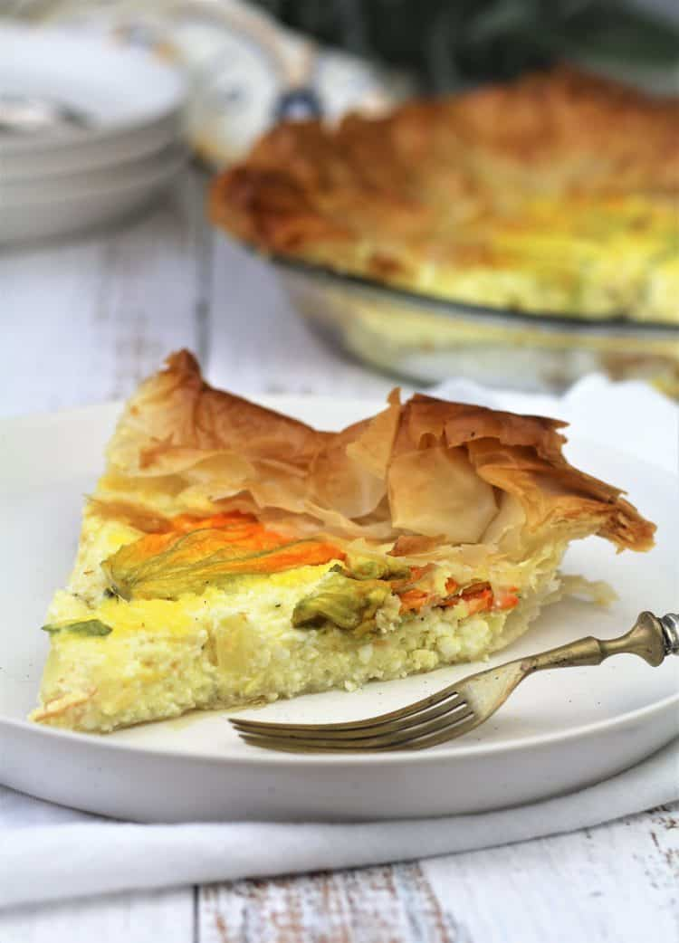 slice of zucchini blossom and ricotta filo tart on white plate with fork