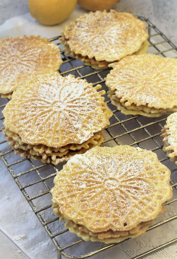 stacked pizzelle dusted with powdered sugar on wire rack