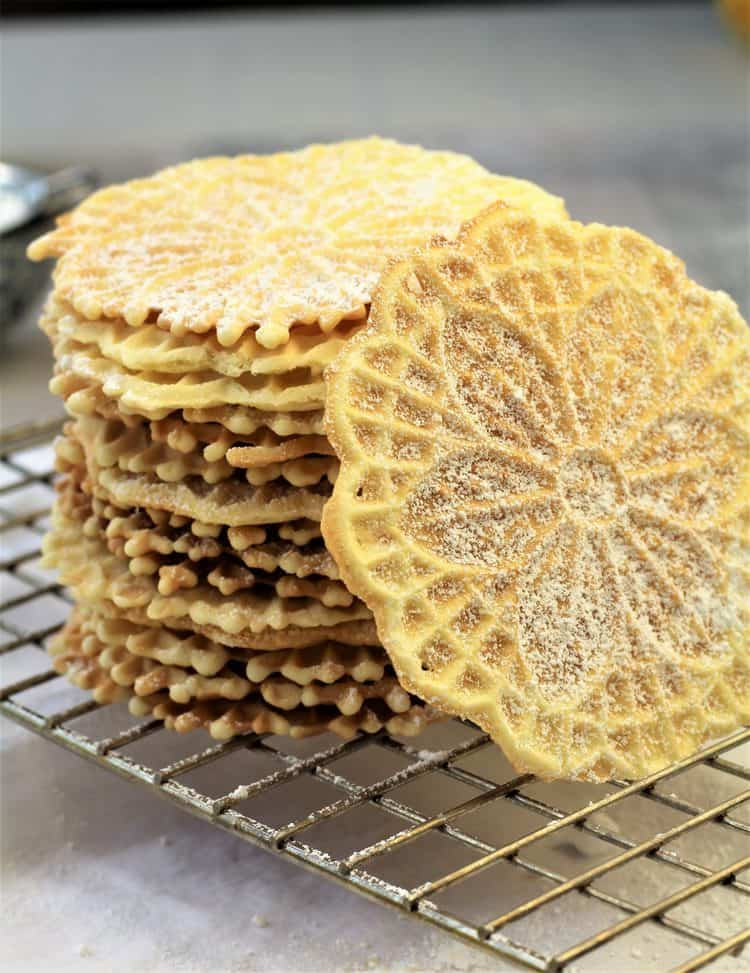 stacked pizzelle cookies dusted with powdered sugar on wire rack with one cookie on side