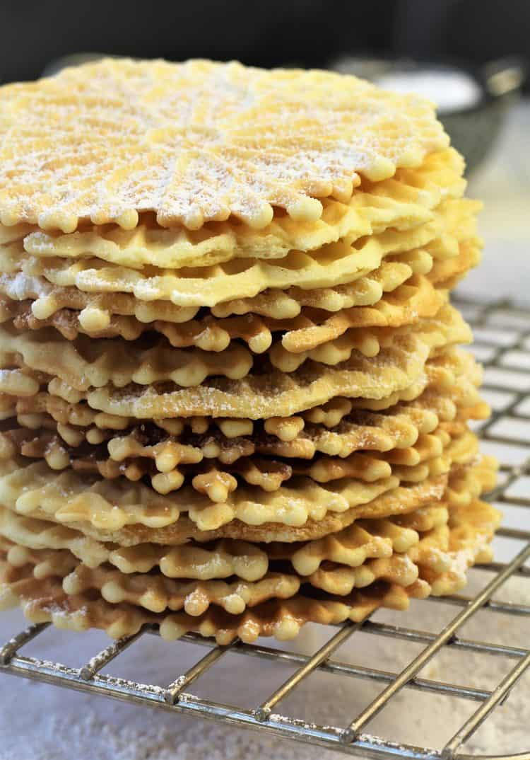 stacked italian pizzelle cookies dusted with powdered sugar on wire rack