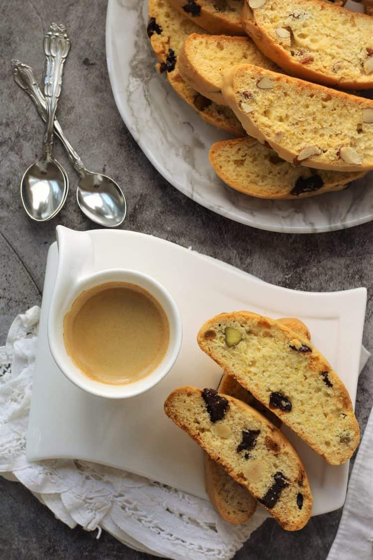 biscotti on plate with cup of coffee with plate of full biscotti in background