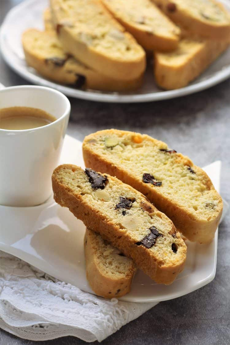 cup of espresso in white cup with biscotti on side and plated in background