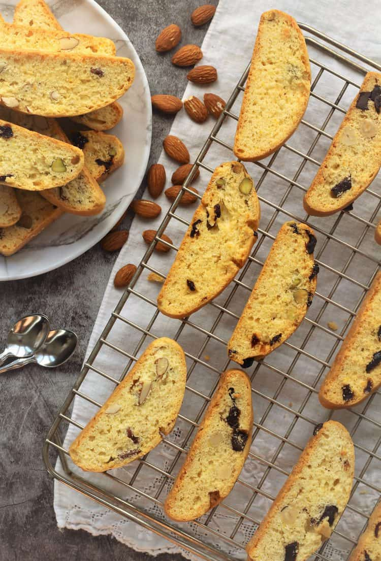 biscotti on wire rack along side plate piled with biscotti
