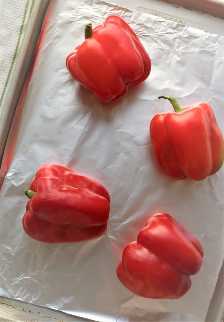 4 red bell peppers on foil lined baking sheet