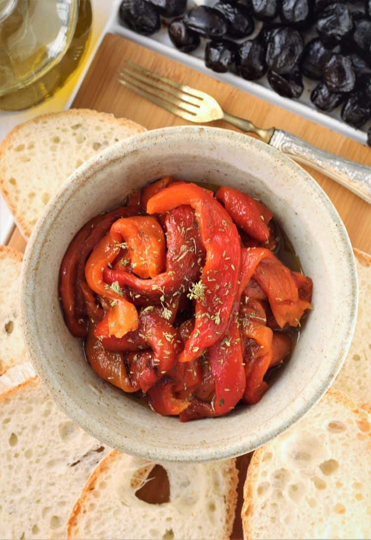 bowl of roasted red bell pepper strips surrounded by bread slices, olives and olive oil