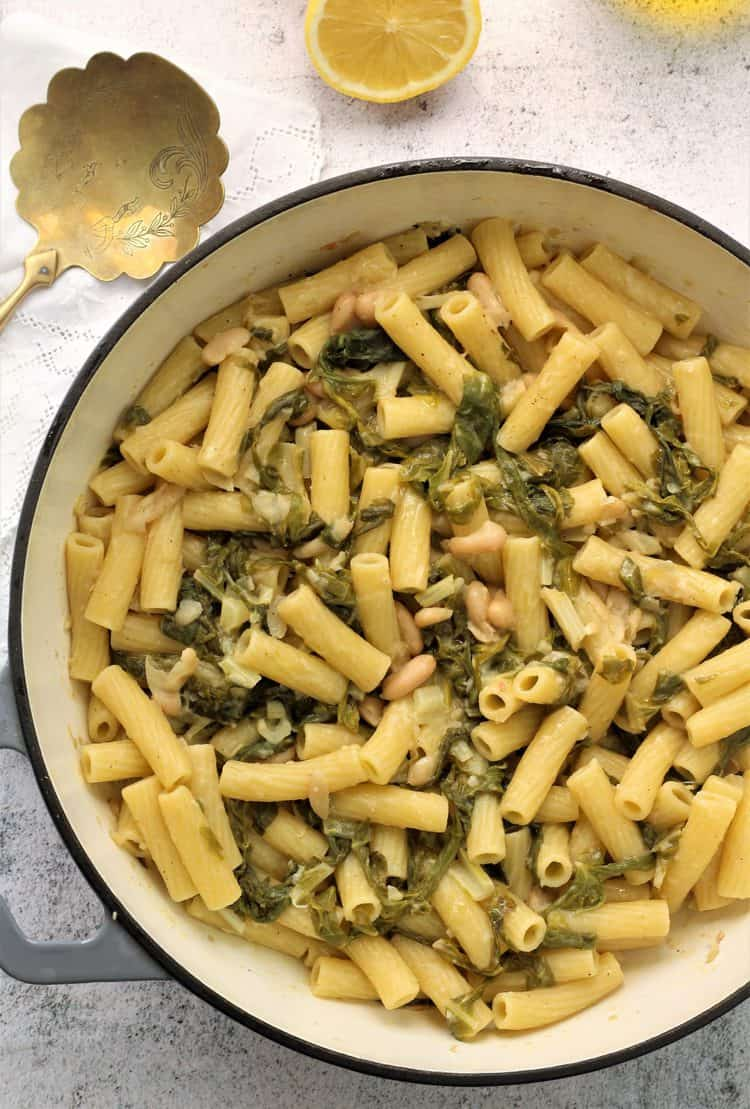 large skillet filled pasta with swiss chard and white beans