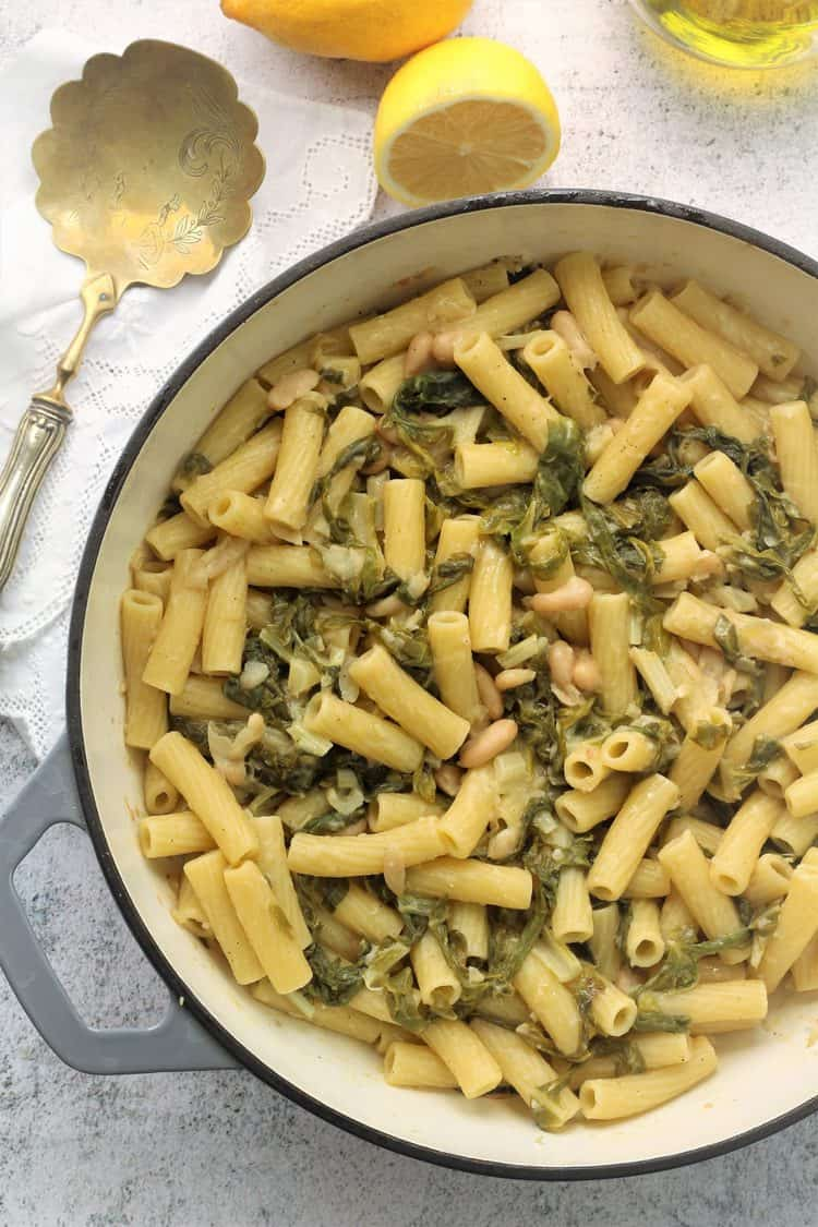 large grey skillet filled with pasta with swiss chard and white beans