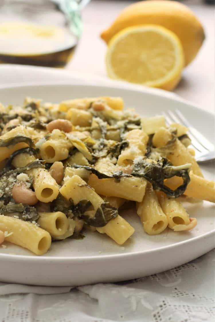 pasta with swiss chard and white beans topped with cheese in white plate