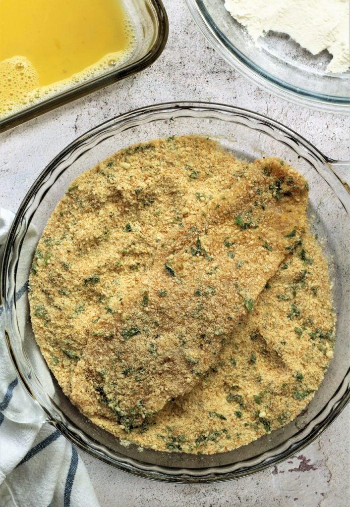 chicken cutlet dredged in bowl of seasoned breadcrumbs