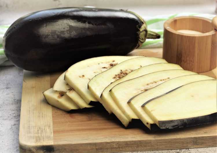 thinly sliced eggplant on wood board with large whole eggplant