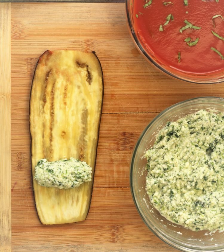 ricotta spinach filling on eggplant slice with bowl of sauce and bowl of spinach ricotta filling