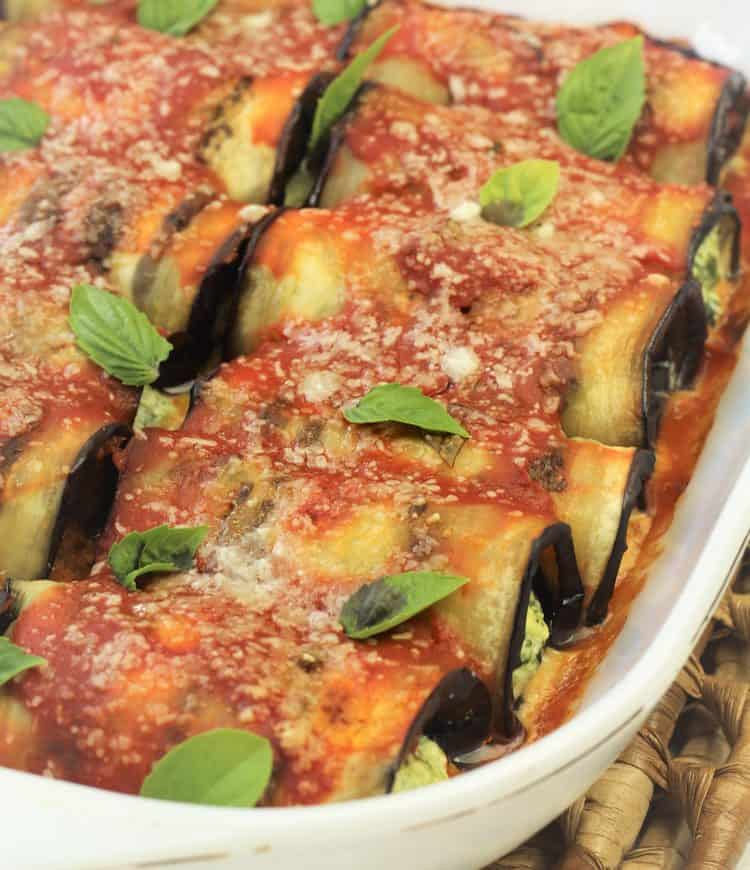 eggplant involtini covered with sauce and basil in baking dish
