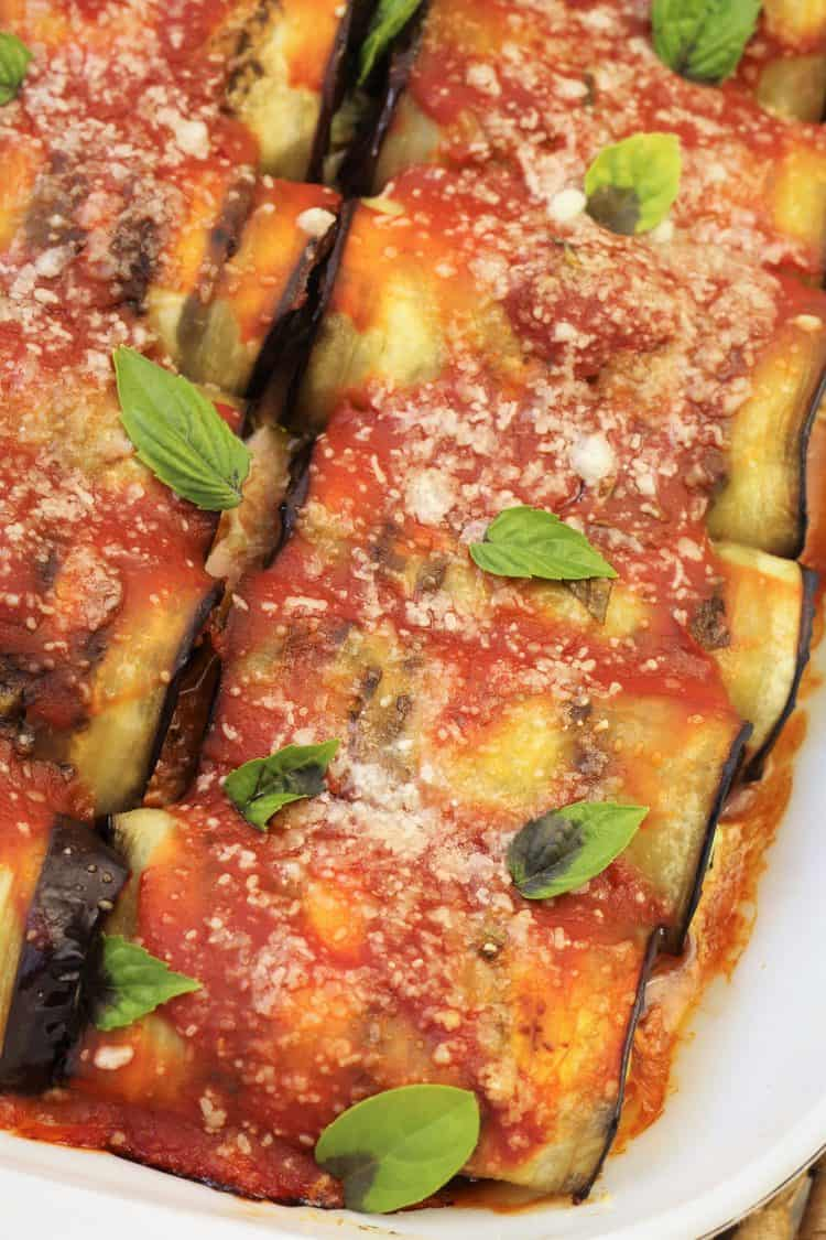 overhead view of eggplant involtini in baking dish with basil leaves on top