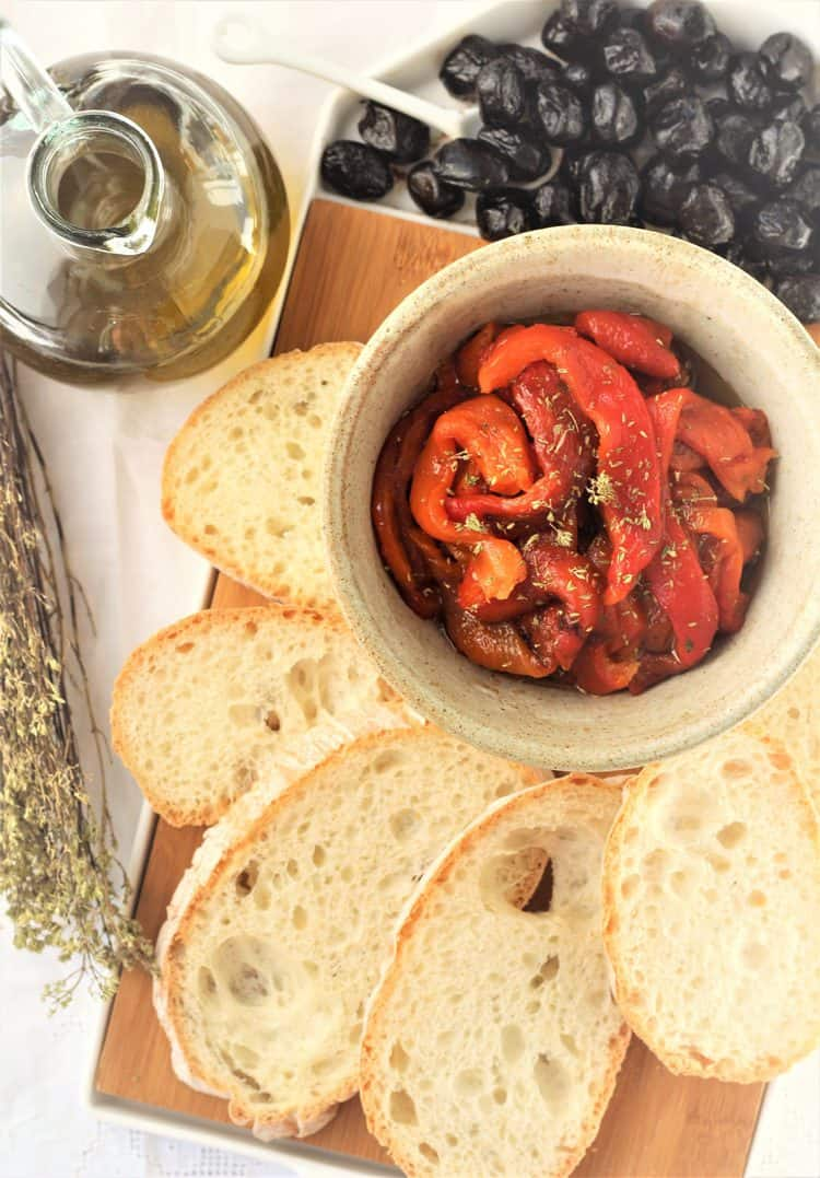 antipasto board with bowl of roasted peppers, bread, olives and olive oil