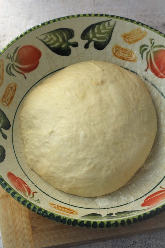 proofed pizza dough in large bowl