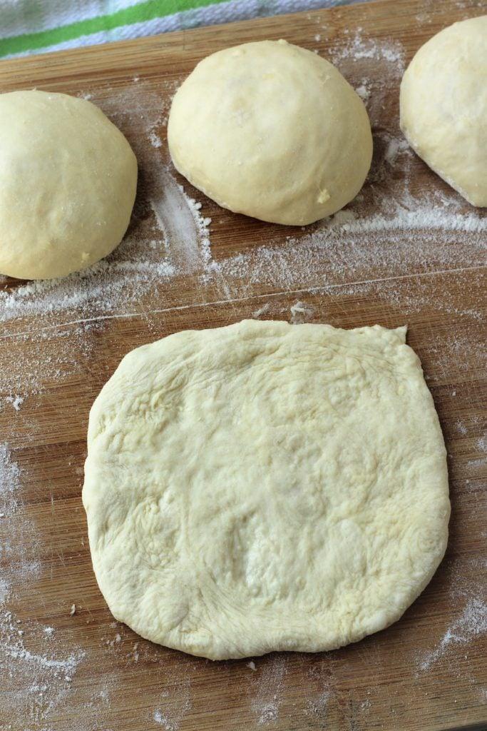 pizza dough ball flattened on wood board