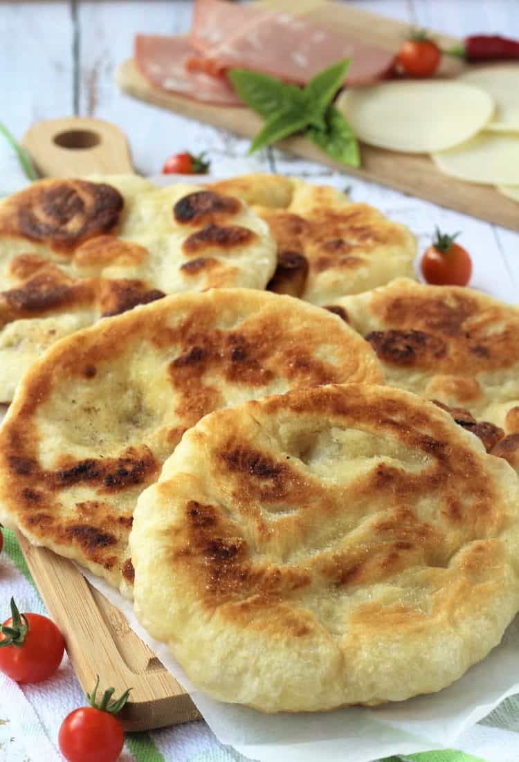 fried pizza dough rounds on wood board served with cherry tomatoes, cheese and mortadella